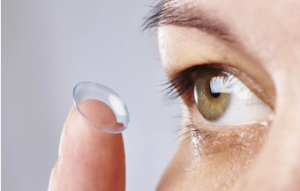 Up close image of someone in the action of inserting a contact lens into their eye.